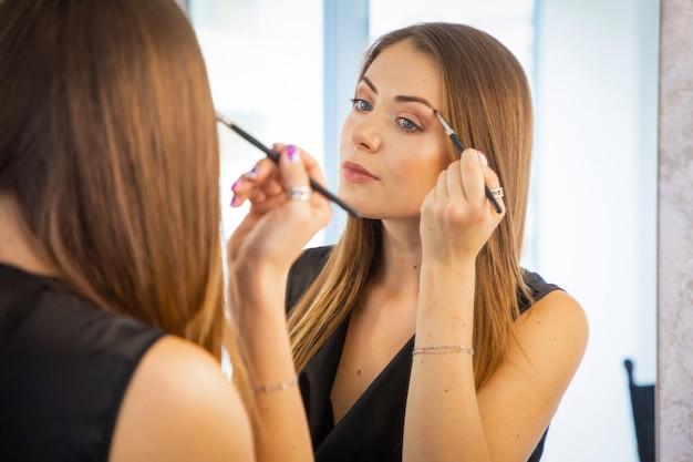 Portret dat van jonge vrouw samenstelling maakt dichtbij spiegel