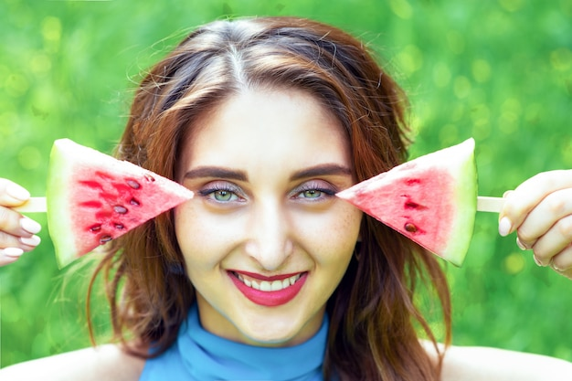 Portret dat van jonge vrouw twee stukken van watermeloen houdt.