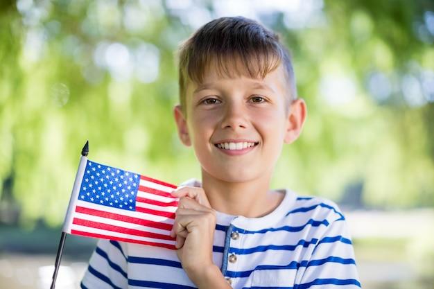 Portret dat van jongen een amerikaanse vlag houdt