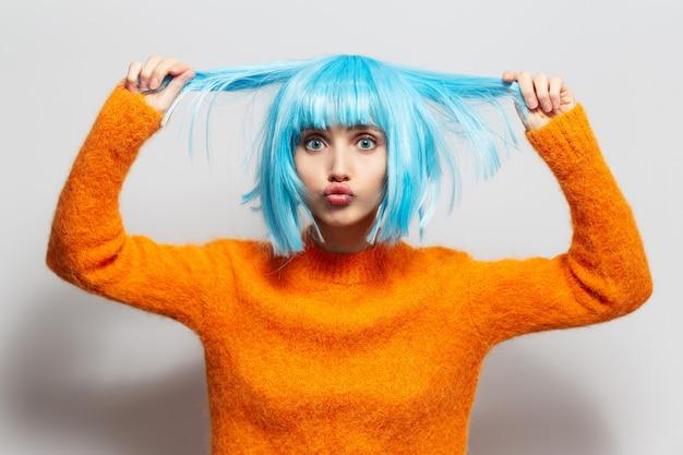 Portret dat van jute-meisje aan het haar van blauwe kleur houdt, oranje sweater draagt tegen witte achtergrond.