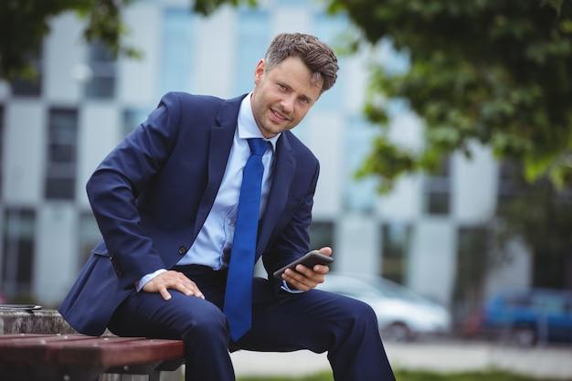 Portret dat van knappe zakenman mobiele telefoon houdt