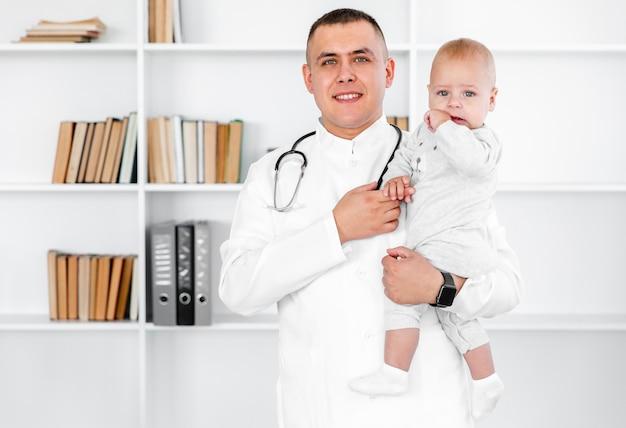 Portret dat van mannelijke arts een baby houdt