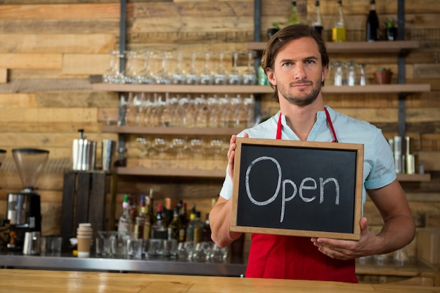 Portret dat van mannelijke barista open uithangbord in coffeeshop houdt