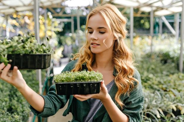 Portret dat van meisje buiten twee plastic pot met groene kleine installaties houdt. jonge vrouwelijke botanicus bestudeert greens.