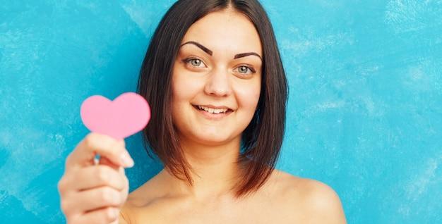 Portret dat van meisje roze document hart houdt.