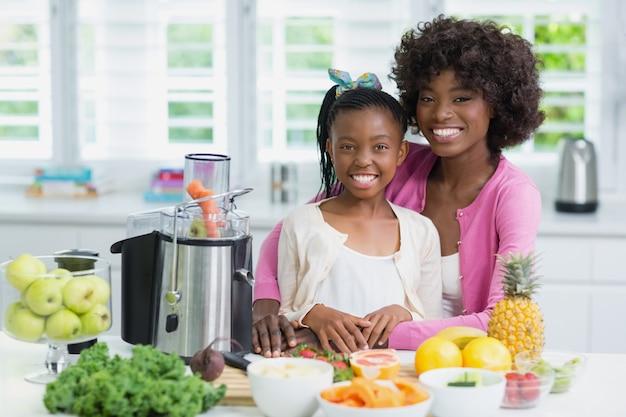 Portret dat van moeder en dochter zich in keuken bevindt