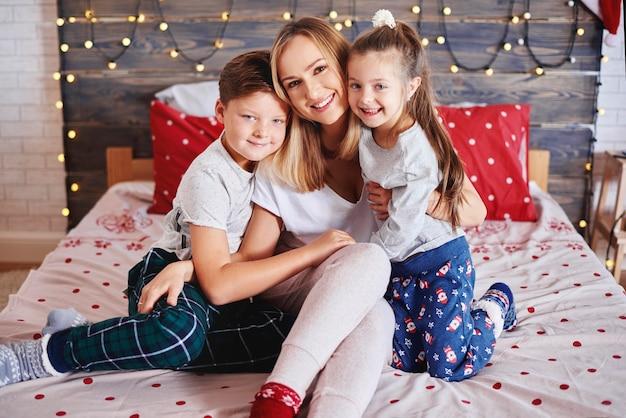 Portret dat van moeder haar kinderen omhelst