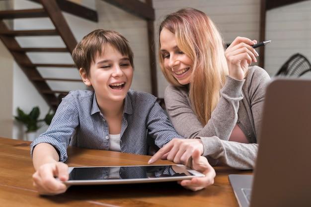 Portret dat van moeder zoon met huiswerk helpt