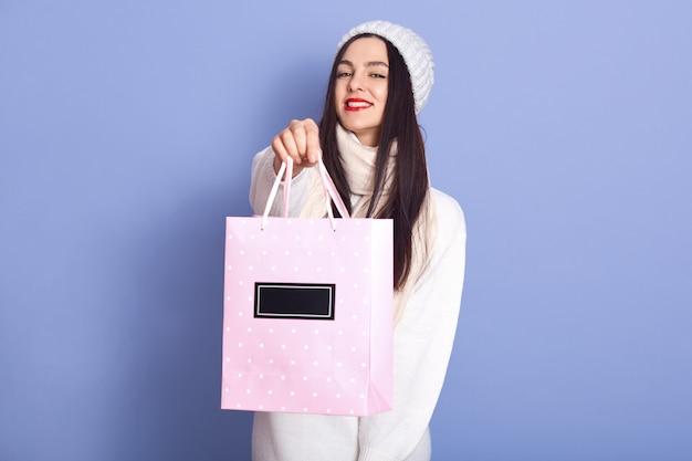 Portret dat van mooi aangenaam wijfje roze document zak met aankoop houdt, die lang zwart haar heeft