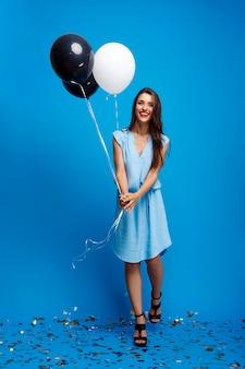 Portret dat van mooi meisje bij partij over blauwe muur rust