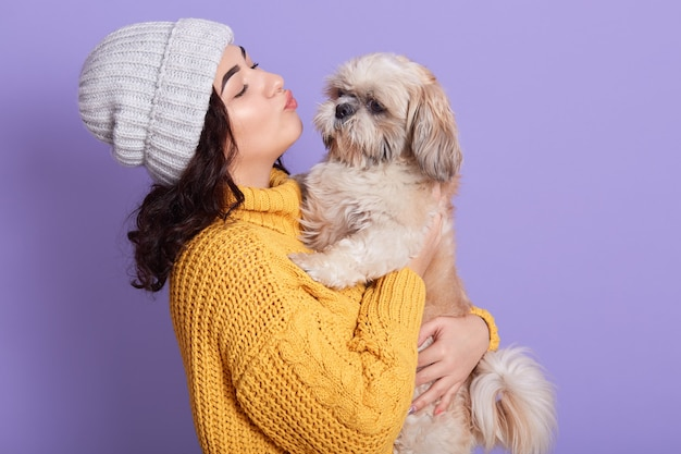 Portret dat van mooi meisje mooie pekingees houdt en hem wil kussen