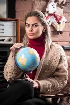 Portret dat van mooie dame een wereldbol houdt