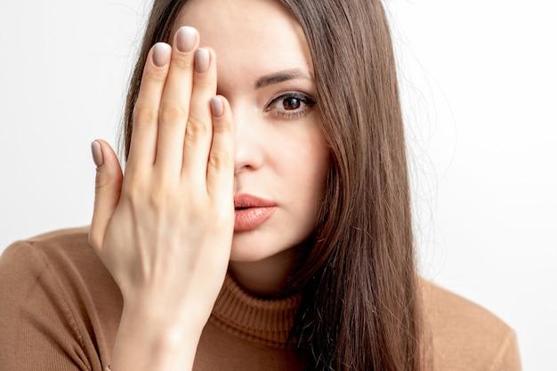 Portret dat van mooie jonge kaukasische vrouw haar half gezicht behandelt met haar hand