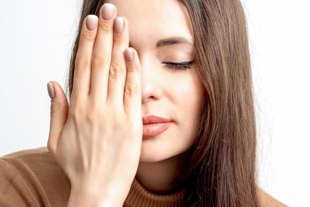 Portret dat van mooie jonge vrouw één oog behandelt door haar hand