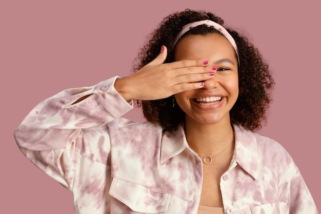 Portret dat van mooie smileyvrouw haar gezicht behandelt met hand