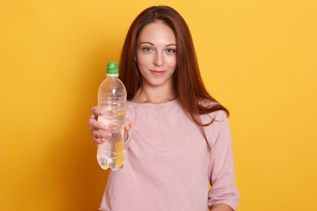 Portret dat van mooie sportenvrouw fles water toont dat op geel wordt geïsoleerd, meisje dat roze overhemd draagt