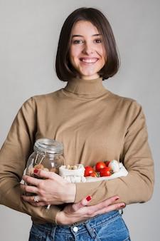 Portret dat van mooie vrouw biologische producten houdt