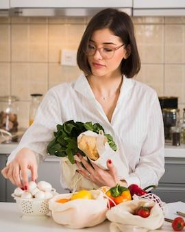 Portret dat van mooie vrouw kruidenierswinkels schikt