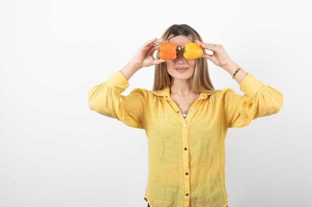 Portret dat van positieve vrouw kleurrijke paprika's voor haar ogen houdt.