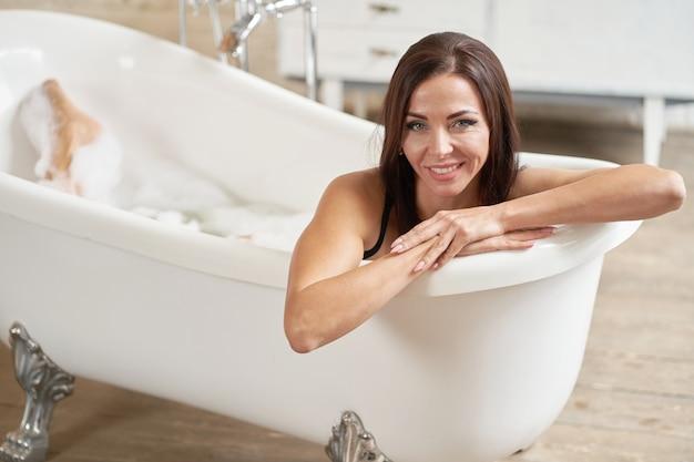 Portret dat van prettige vrouw genoegen in bad neemt