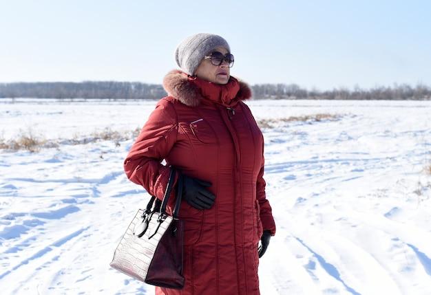 Portret dat van russische hogere vrouw weg tegen sneeuwgebied kijkt