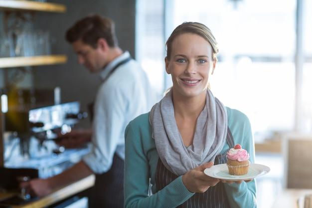 Portret dat van serveerster een plaat van cupcake houdt