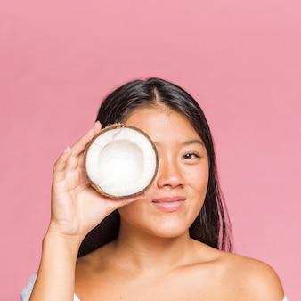 Portret dat van smileyvrouw een kokosnoot houdt