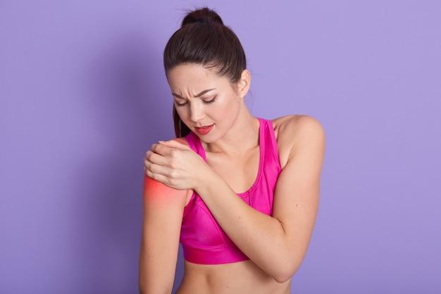 Portret dat van sportieve vrouw haar hand op verwondingsschouder zet, die pijn heeft. sportvrouw met pijnlijke gezichtsuitdrukking die roze bovenkant draagt