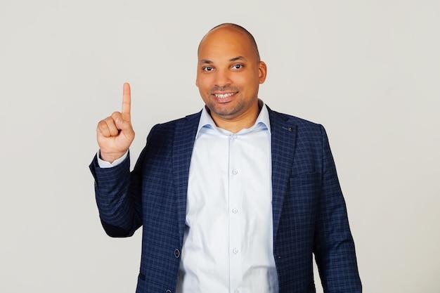 Portret dat van succesvolle jonge afrikaanse amerikaanse zakenmankerel, nummer één vingers toont, glimlachend, zelfverzekerd en gelukkig. de man toont een vinger. nummer 1