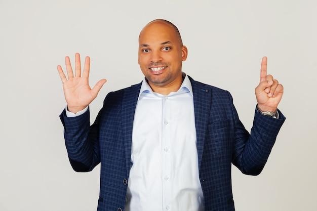 Portret dat van succesvolle jonge afrikaanse amerikaanse zakenmankerel, nummer zes met vingers toont, glimlachend, zelfverzekerd en gelukkig. de man toont zes vingers. nummer 6.