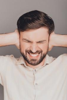 Portret dat van trieste zakenman oren behandelt van lawaai