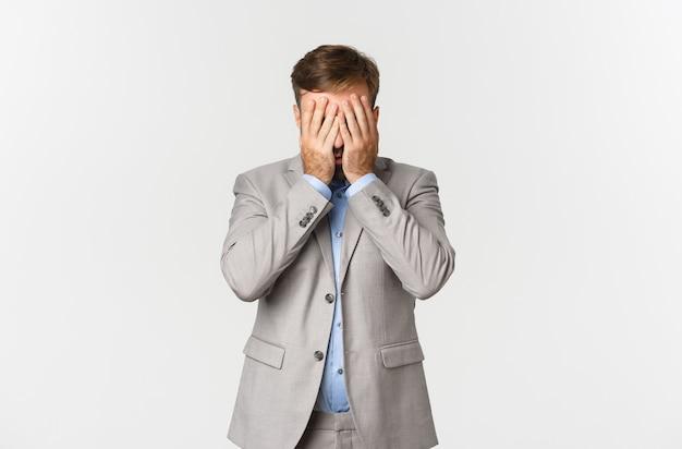 Portret dat van verontruste en uitgeputte zakenman, zijn gezicht achter handen verbergt