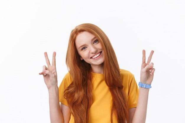 Portret dat van vrolijke jonge vrouw twee vingers of overwinningsgebaar toont, over grijs