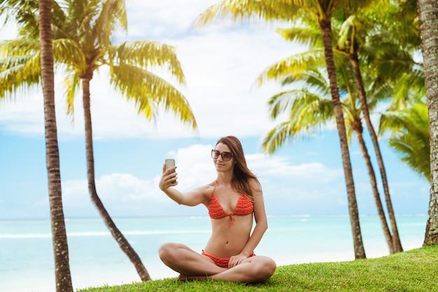 Portret dat van vrolijke vrouw selfie onder palm neemt