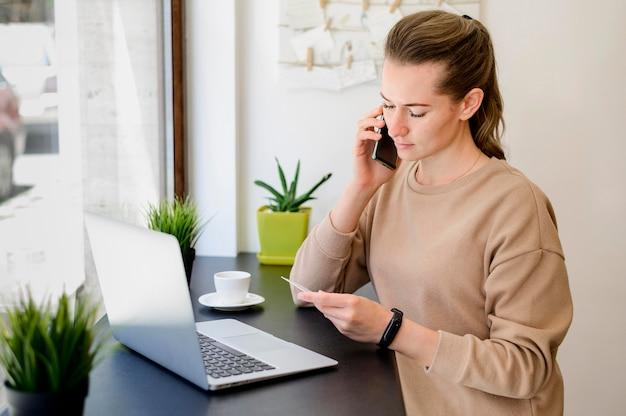 Portret dat van vrouw creditcarddetails op de telefoon geeft
