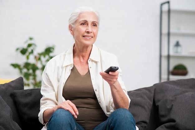 Portret dat van vrouw een afstandsbediening houdt