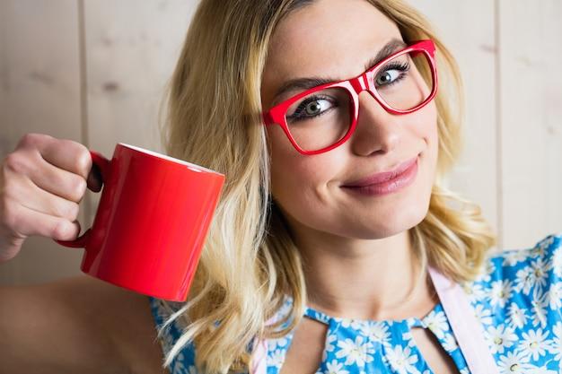 Portret dat van vrouw een koffiemok houdt