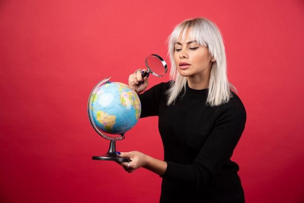 Portret dat van vrouw een vergrootglas en de bol van de aarde houdt.