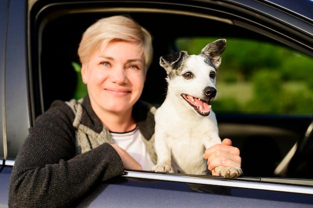 Portret dat van vrouw haar hond voor een rit neemt