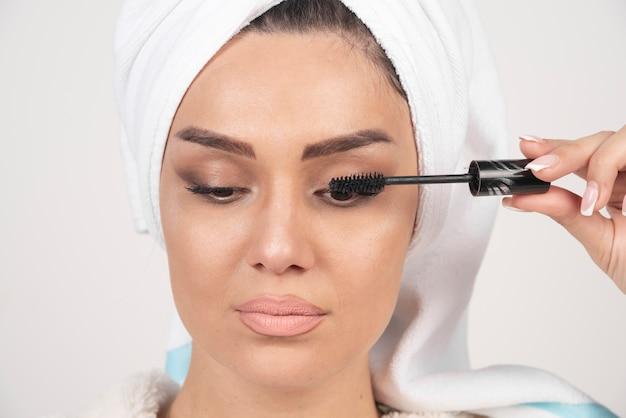 Portret dat van vrouw in witte handdoek wordt verpakt die mascara toepast.
