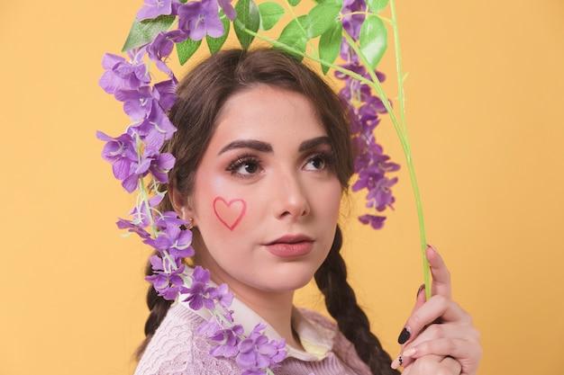 Portret dat van vrouw purpere bloem houdt rond haar hoofd