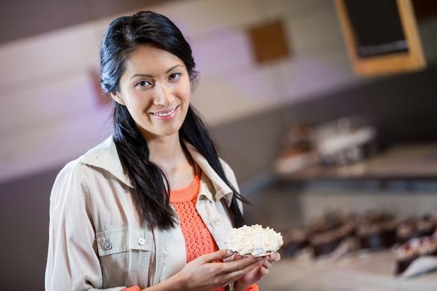 Portret dat van vrouw zoet voedsel houdt