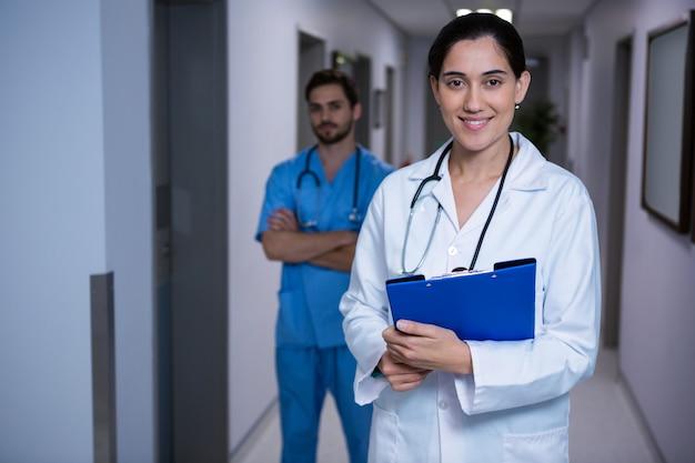 Portret dat van vrouwelijke arts zich met verpleegster op achtergrond bevindt