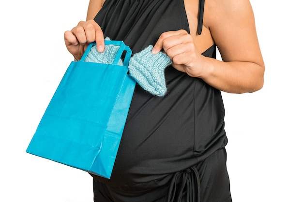 Portret dat van zwangere vrouw een gift voor nieuwe baby opent tegen witte muur. moederschap en zwanger concept.