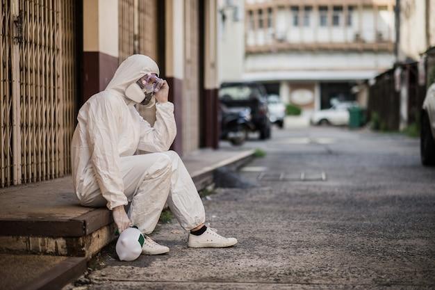 Portret desinfectiespecialist man in pbm-pak, handschoenen, masker en gelaatsscherm die openbare decontaminatie uitvoert, zittend met een moe gevoel tijdens ontsmettingsmiddel om covid-19 te verwijderen