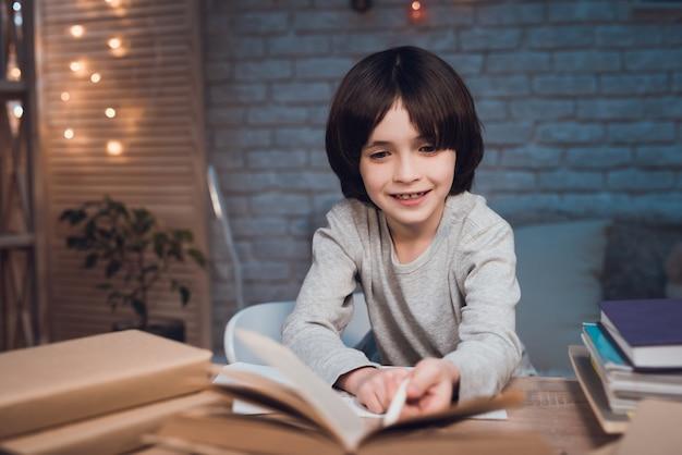 Portret die gelukkige schooljongen glimlachen die huiswerk doen