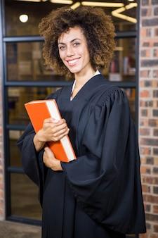 Portret die van advocaat zich dichtbij bibliotheek met wetsboek bevinden in bureau