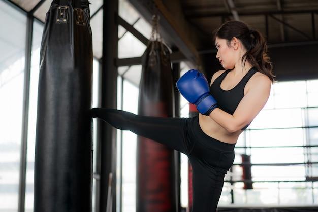 Portret die van aziatische zekere jonge bokservrouw met blauwe bokshandschoenen, een zak in dozen doend in professioal gymnastiek schoppen. sportief geschikt voor gezonde levensstijl aziatische model van boks gym concept.