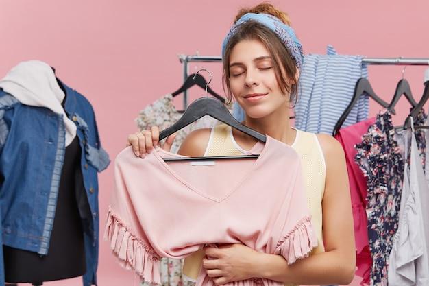 Portret die van blije vrouw zich in paskamer bevinden, modieuze kleding houden, haar ogen met plezier sluiten, die met nieuwe aankoop tevreden zijn. vrouwelijke klant die in klerenwinkel kleding voor zich kiezen