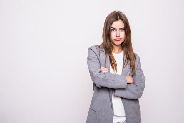 Portret die van boze vrouw zich met gevouwen wapens bevinden geïsoleerd op grijze achtergrond